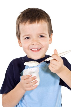 hungry children: Healthy happy boy eating yogurt - isolated