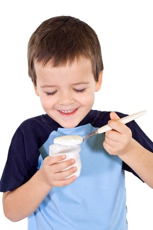 balanced diet: Happy healthy boy eating yogurt - isolated