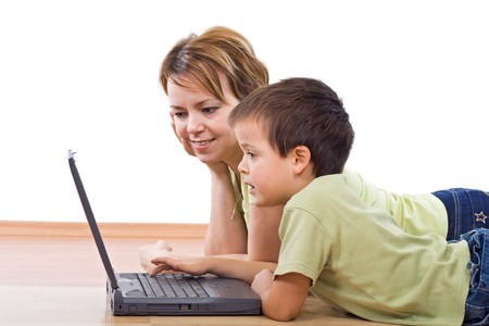 Child surfing the net under supervision - isolated, focus on the boy face Stock Photo - 4340544