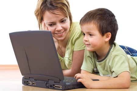 Surfing the web - woman and little boy laying on the floor with a laptop - isolated Stock Photo - 4340572