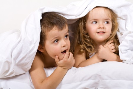 bedding indoors: Kids playing under the quilt - focus on the boy