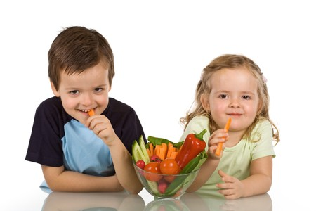 Happy kids with a bowl of vegetables, smiling and eating carrot - isolated Stock Photo