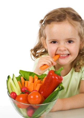 Happy healthy little girl eating vegetables - chomping a carrot - isolated photo