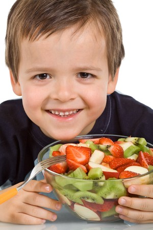 Happy smiling kid holding a large bowl of fruit salad - isolated, closeup photo