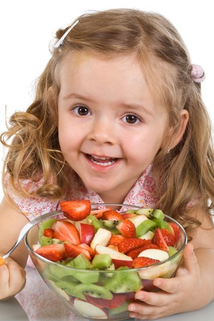 Happy little girl holding a bowl of mixed fruit salad - isolated photo