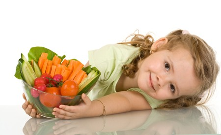 carrots isolated: Little girl leaning on the table with a bowl of vegetables - isolated