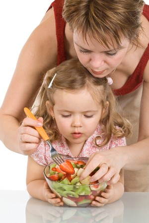 Little girl and her mother preparing fruit salad - isolated photo