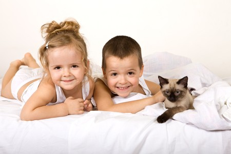 Happy kids playing with their kitten in the bed Stock Photo - 4448945