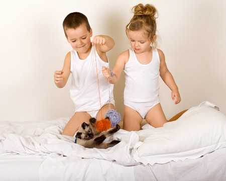 string together: Kids playing on the bed with a kitten and yarn balls