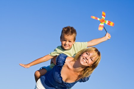 Woman and little boy playing with windmill toy against blue summer sky photo