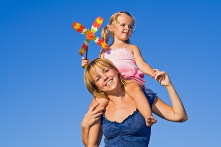 Woman and little girl against summer sky playing with windmill toy photo