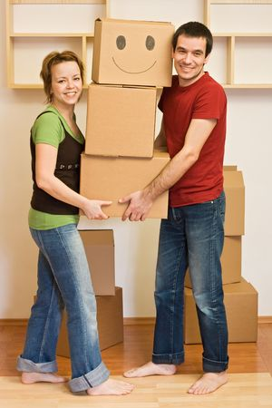 Happy couple carrying cardboard boxes moving into a new home photo