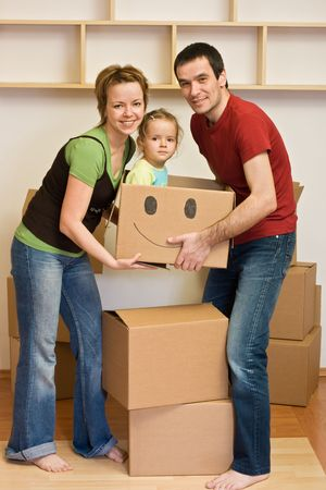 lift and carry: Happy family with a kid moving into a new home - lifting cardboard boxes