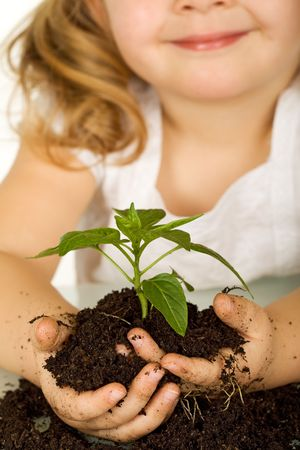 nalatenschap: Meisje bedrijf een jonge plant in de bodem, lachend - close-up