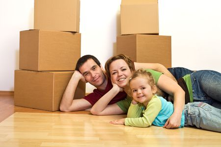 Happy family laying on the floor in their new home with cardboard boxes in the background photo