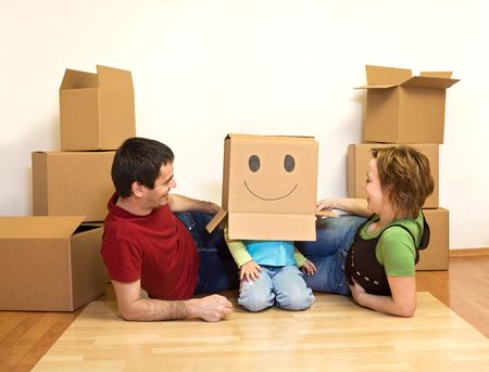 Happy young family playing with cardboard boxes on the floor of their new home - moving concept Stock Photo - 4653276