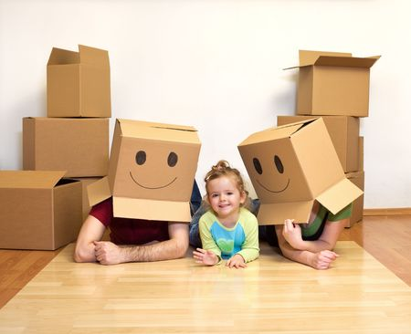 Happy family playing with cardboard boxes on the floor in their new home Stock Photo