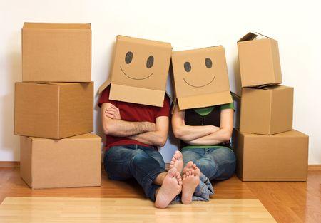 cardboard: Couple heureux dans leur nouvelle maison en s'amusant - concept en mouvement Banque d'images