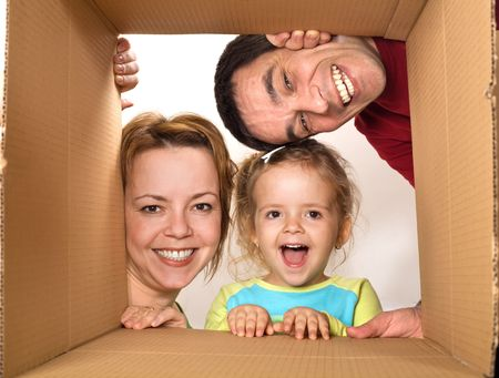 Happy family opening cardboard box - moving concept Stock Photo