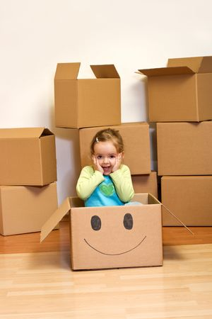 Little girl in cardboard box with a smiley - moving concept photo