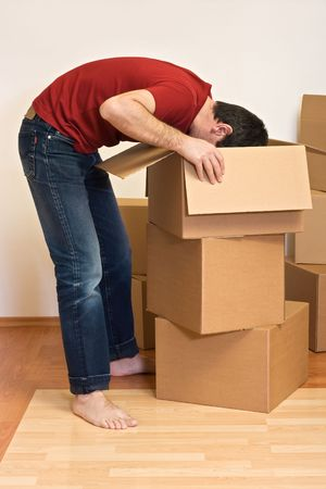 Man unpacking from cardboard boxes in a new home - moving concept Stock Photo - 4761903