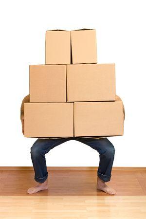 Man kämpft beim Heben viele Kartons - die beweglichen Konzept Standard-Bild