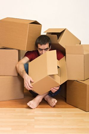 Man under lots of cardboard boxes on the floor - moving concept Stock Photo - 4761871