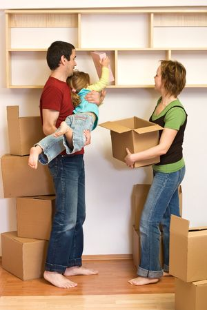 Family unpacking with lots of cardboard boxes - moving concept photo