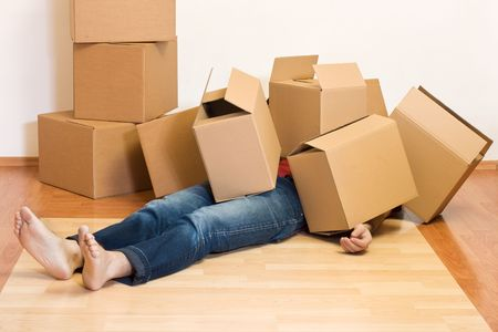 Man covered by lots of cardboard boxes - moving concept photo