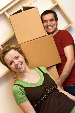 happy couple at home: Enjoy the chaos of moving - happy couple with cardboard boxes Stock Photo