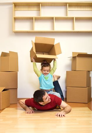 good times: Moving to a new home is fun - kid and father having good times with lots of cardboard boxes