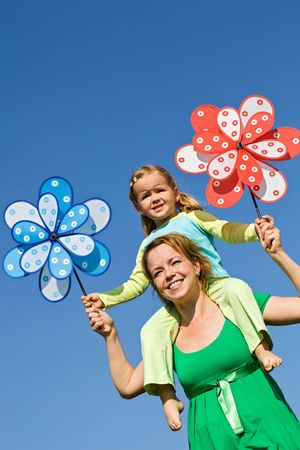 Woman and little girl having fun with windmill toys outdoors in the spring