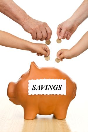 Financial education and money savings concept, isolated - hands of different generations putting coins into a piggy bank Stock Photo