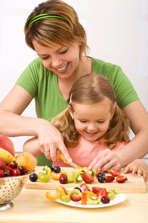 Little girl and her mom having fun preparing summer fruits salad photo