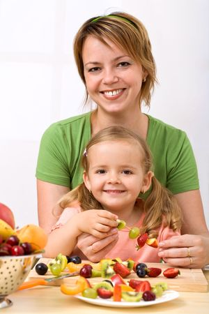 Happy healthy woman and little girl making summer fruits kebab photo