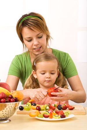 Woman and little girl slicing fruits preparing a healthy snack photo