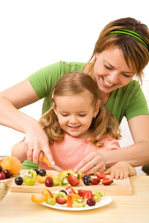 Happy woman and little girl slicing fruits for a healthy salad photo
