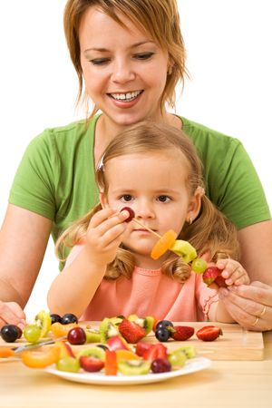 Woman and little girl preparing fruit slices on wooden sticks for a healthy snack - isolated photo