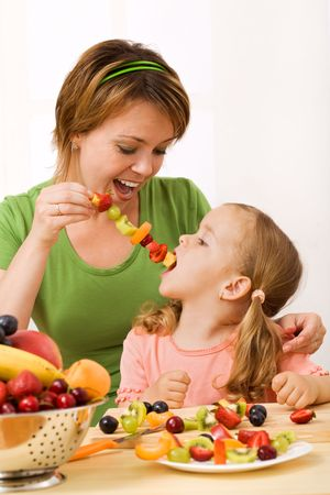 Girls having fun eating fruit slices from a stick - healthy snack concept