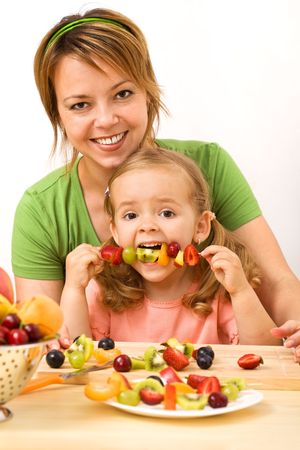 Woman and little girl eating fruit slices on a stick - healthy snack photo