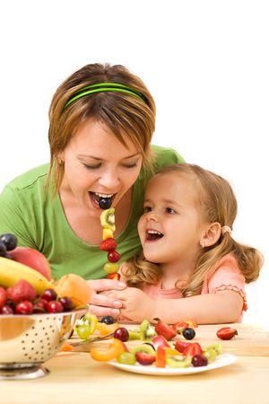 frutas divertidas: Mujer y ni�a comiendo frutas rebanadas en un palo