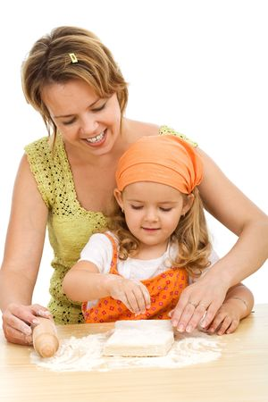 Woman teaching little girl how to stretch the dough making a cake - isolated photo