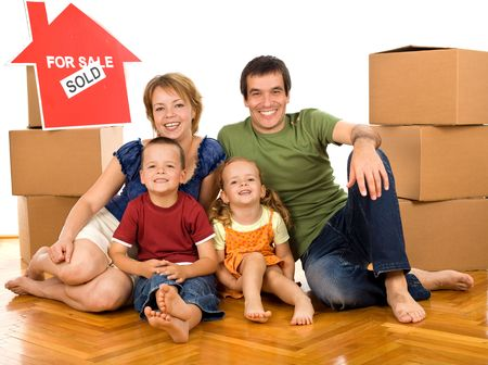 Happy family on the floor with cardboard boxes moving in their new home - isolated photo