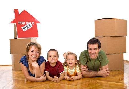 Happy family laying on the floor in their new home - isolated photo
