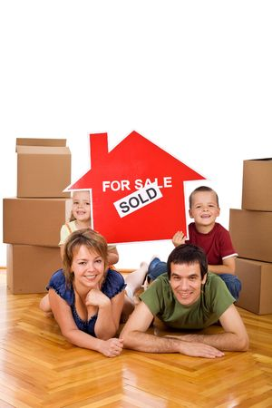 Happy family posing with the house sold sign on the floor of their new home - isolated photo