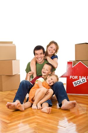 unpacking: Happy couple with two kids having fun on the floor in their newly bought home - isolated