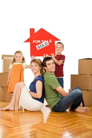 Happy family with cardboard boxes in their new home showing the house sold sign - isolated photo