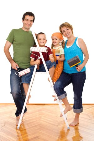 Happy family with painting utensils ready to repaint their home - isolated photo