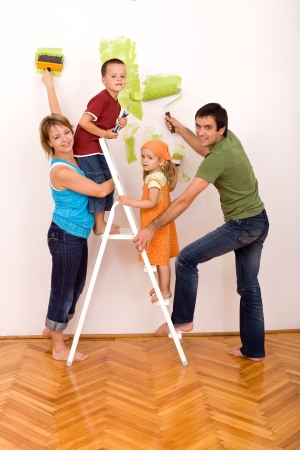 redecorating: Happy family with two kids holding brushes and painting rolls redecorating their home together