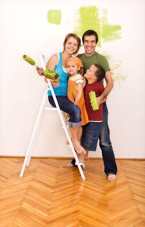 一緒に彼らの新しい家を塗装梯子の上の 2 人の子供の幸せな家族